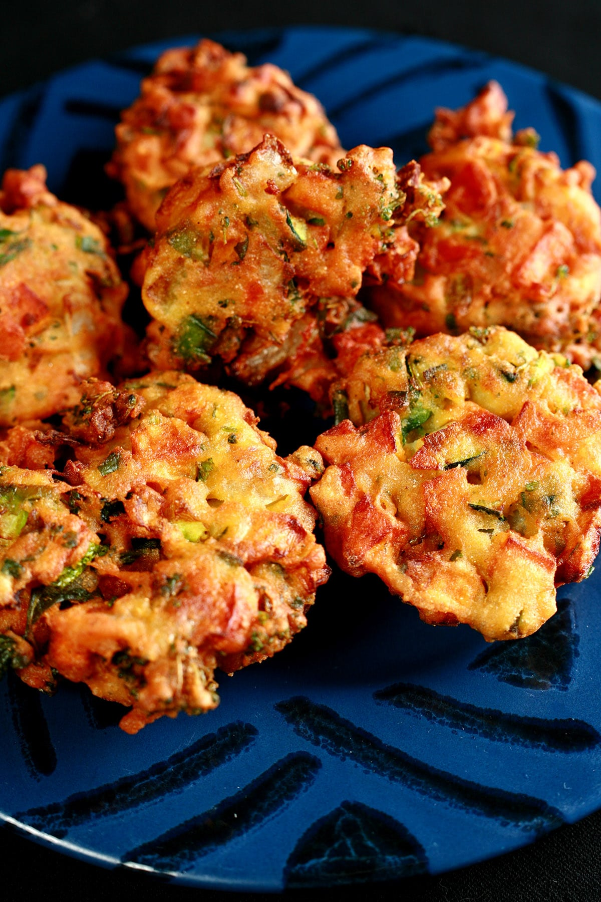 A close up view of mixed veggie pakora. They are little patties of sweet potatoes, onions, broccoli, cilantro, and more, in a curried batter, deep fried.