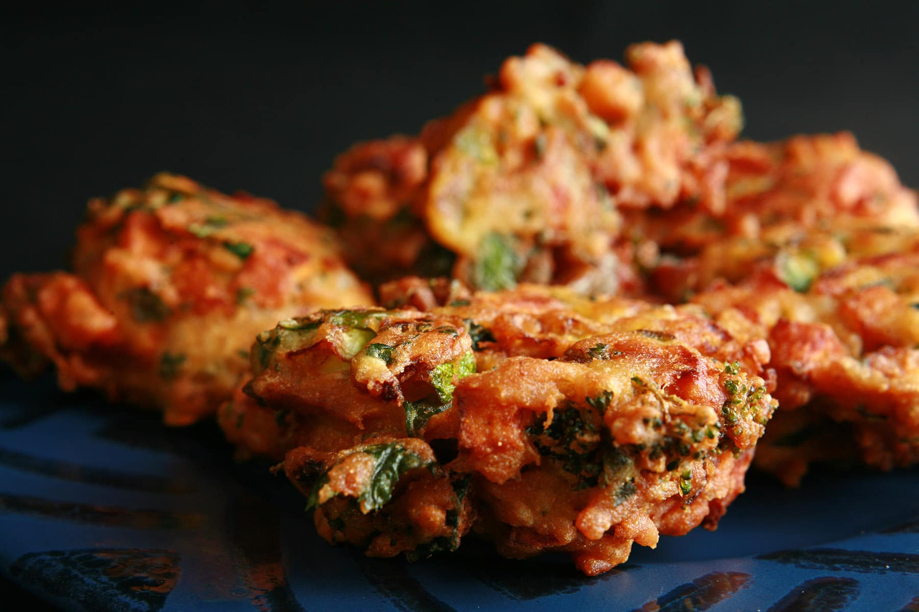 A close up view of mixed vegetable pakora. They are little patties of sweet potatoes, onions, broccoli, cilantro, and more, in a curried batter, deep fried.