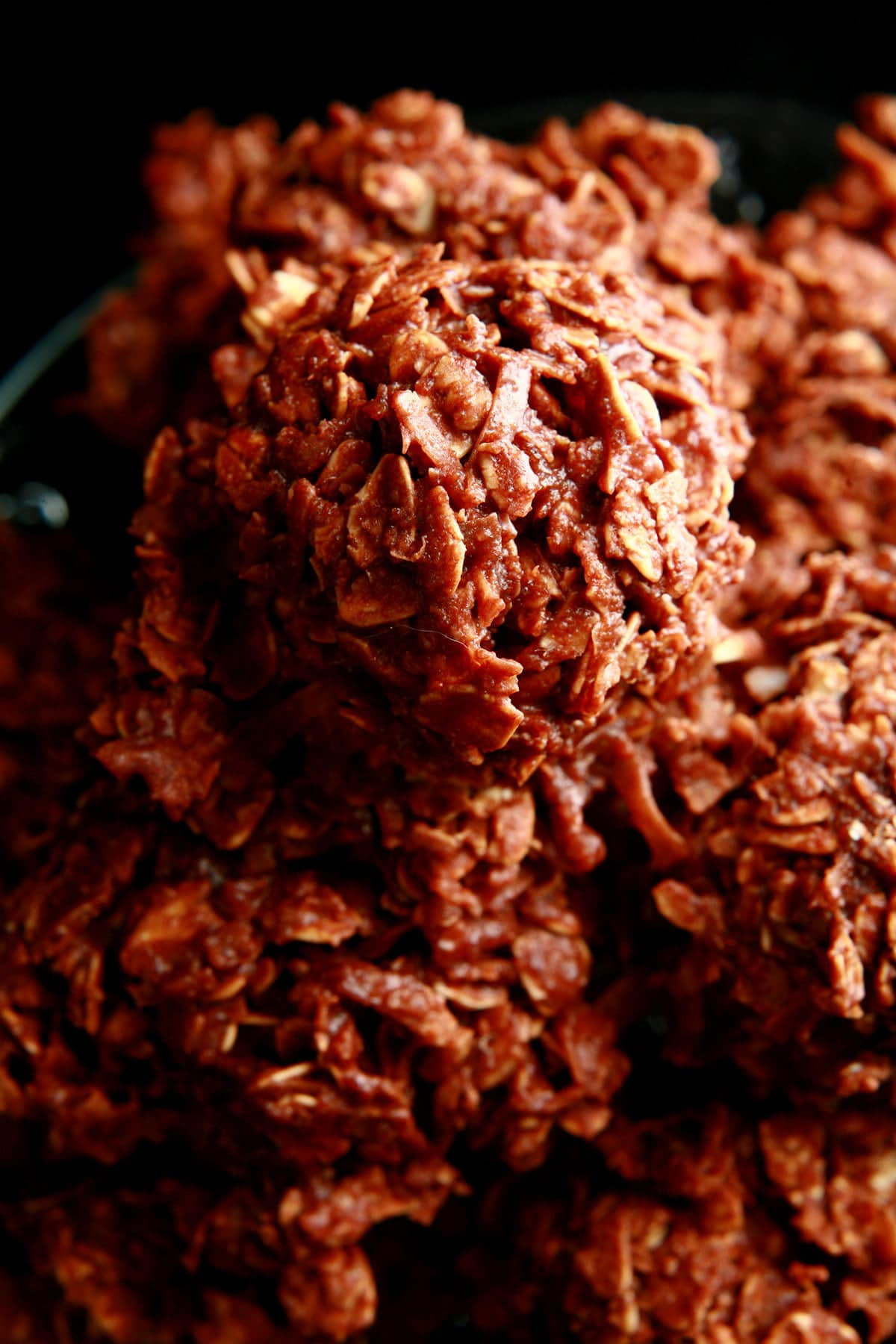 A small plate is piled high with chocolate no-bake cookies. The oats and coconut are visible, completely covered in chocolate.