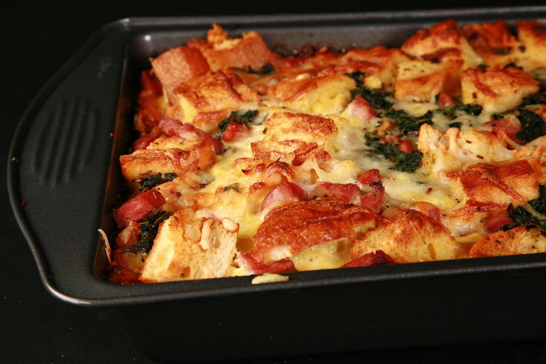 A full pan of freshly baked ham, kale, and swiss strata.