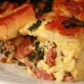 A large square serving of ham, kale, and swiss strata on a white plate.