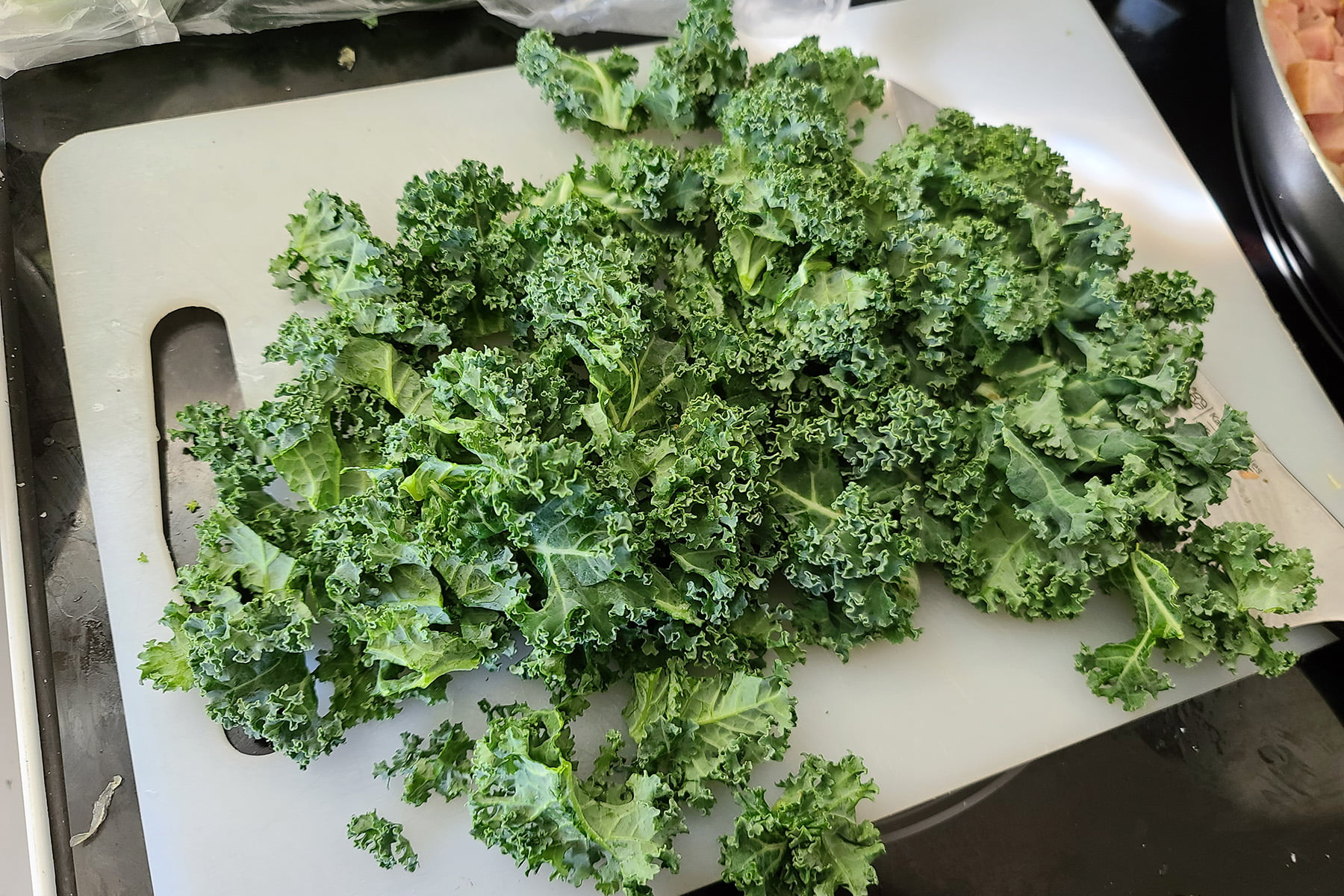A pile of fresh kale on a cutting board.