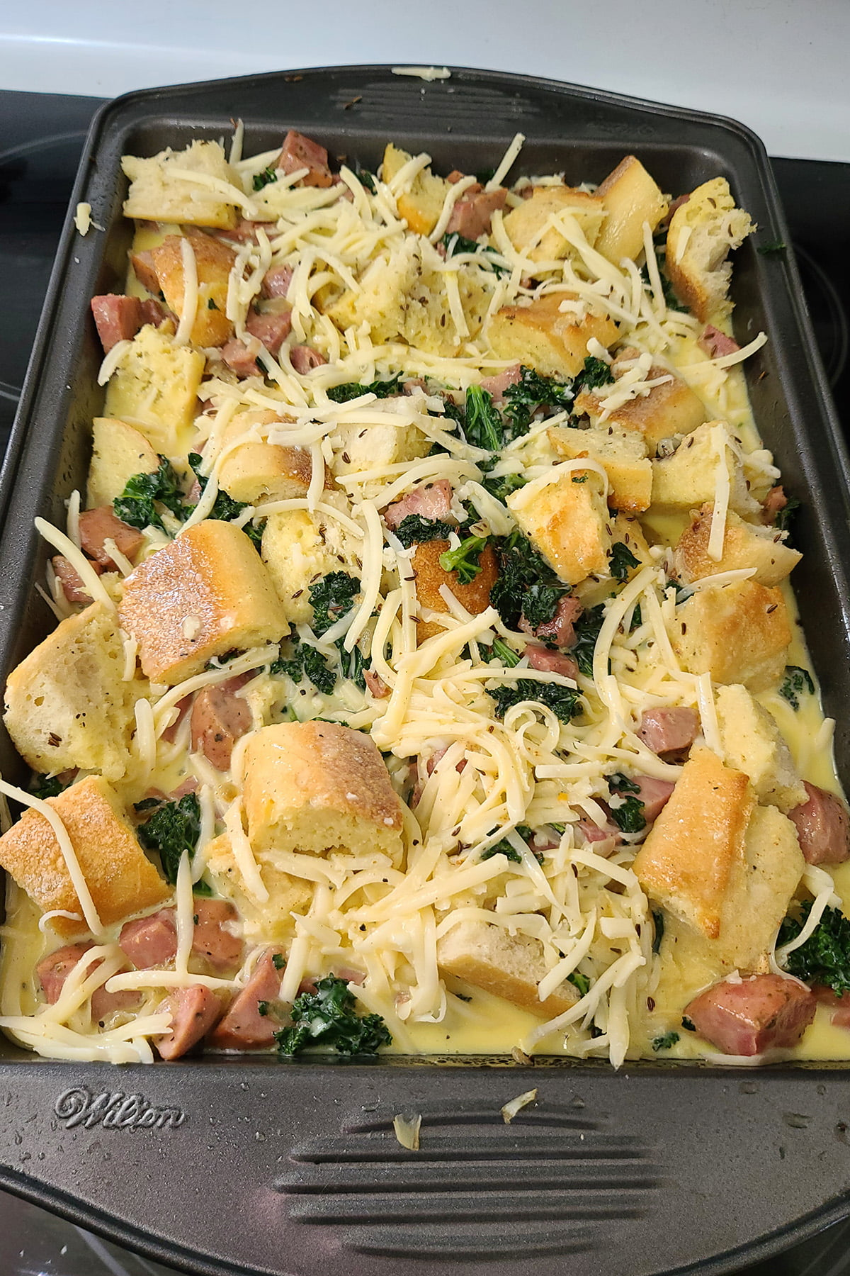 A pan of unbaked kale and ham strata.