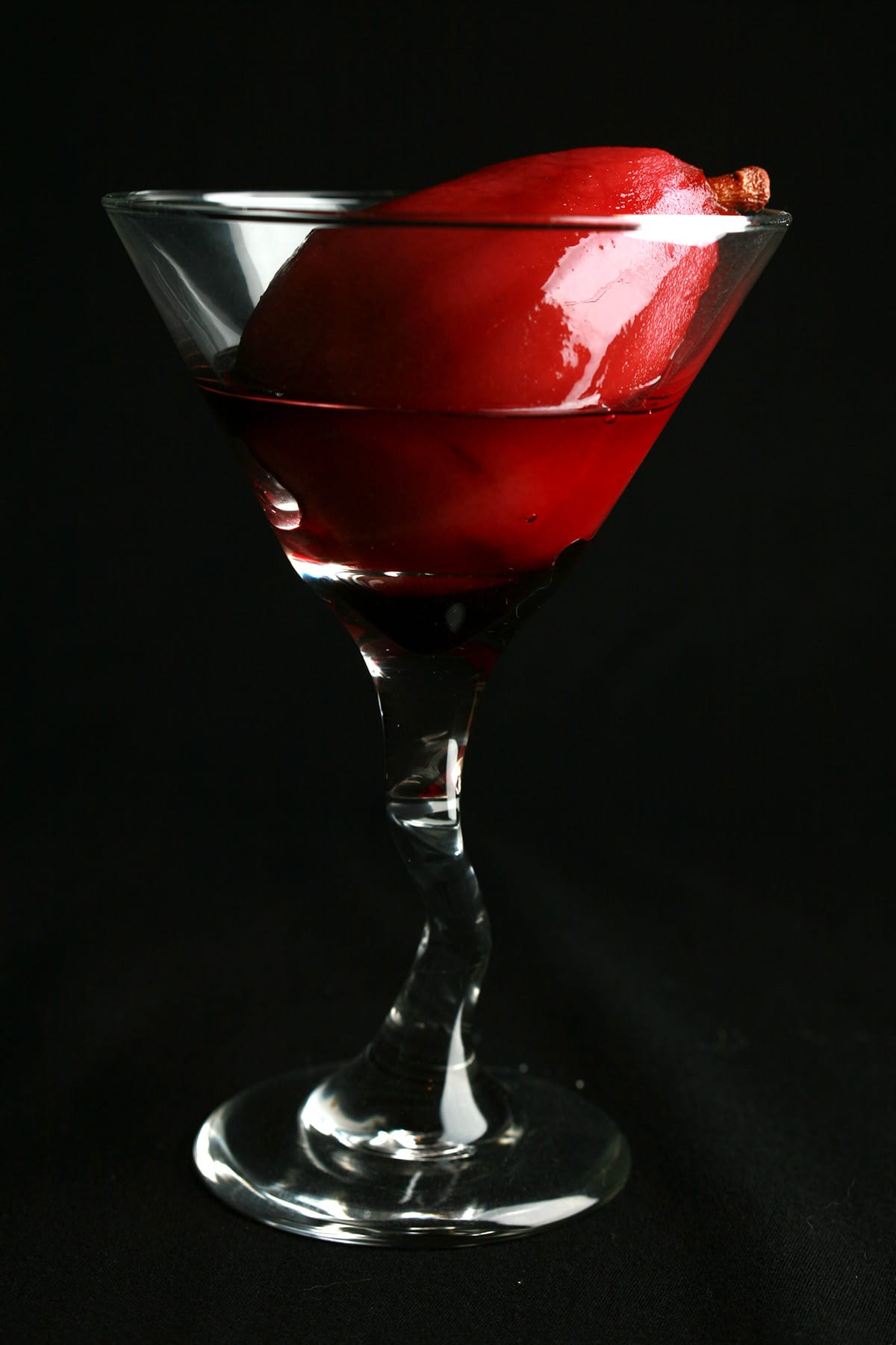 A single wine poached pear in a Martini glass.
