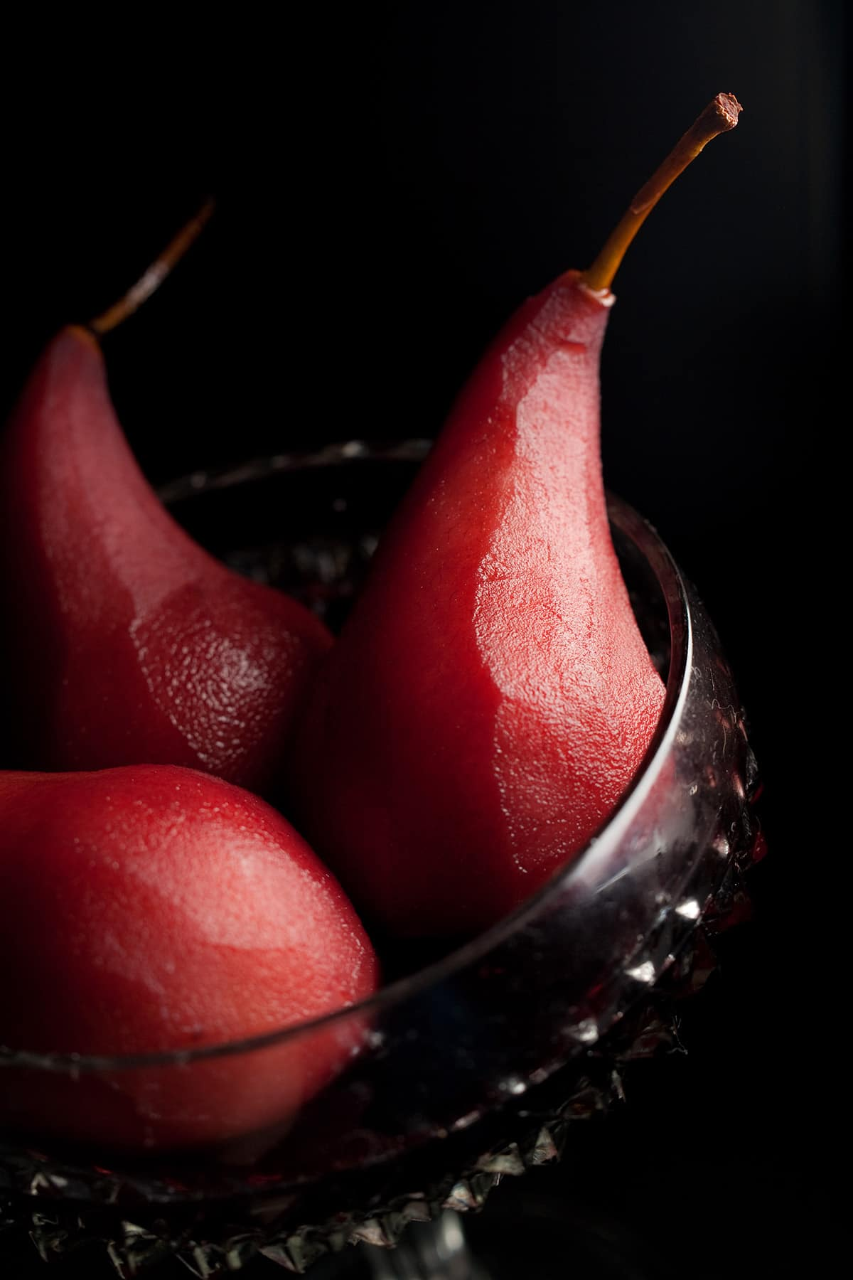 3 wine poached pears in a large, faceted goblet.