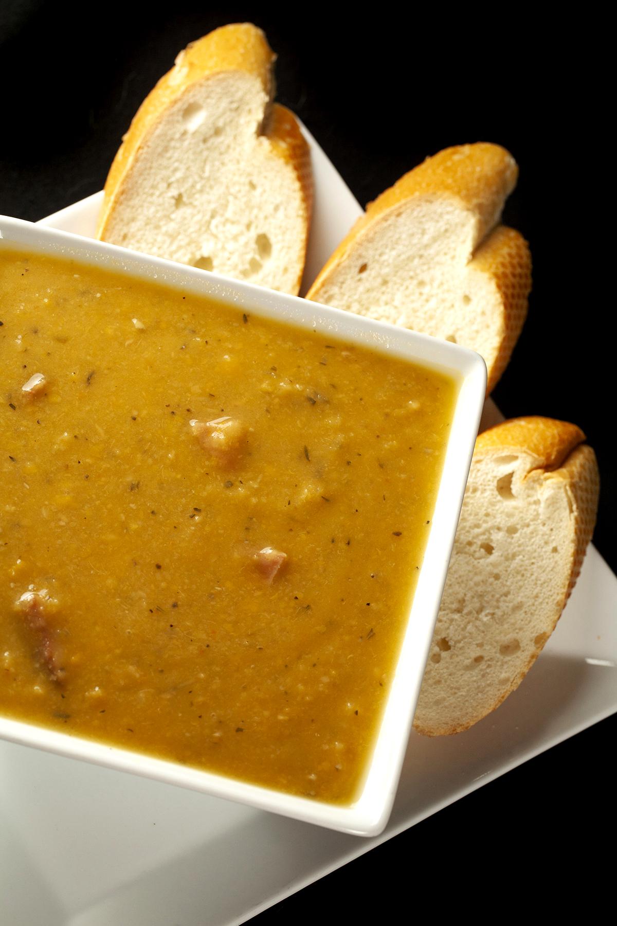 A white, square shaped bowl of smooth French Canadian Pea Soup, with sliced baguette next to it.