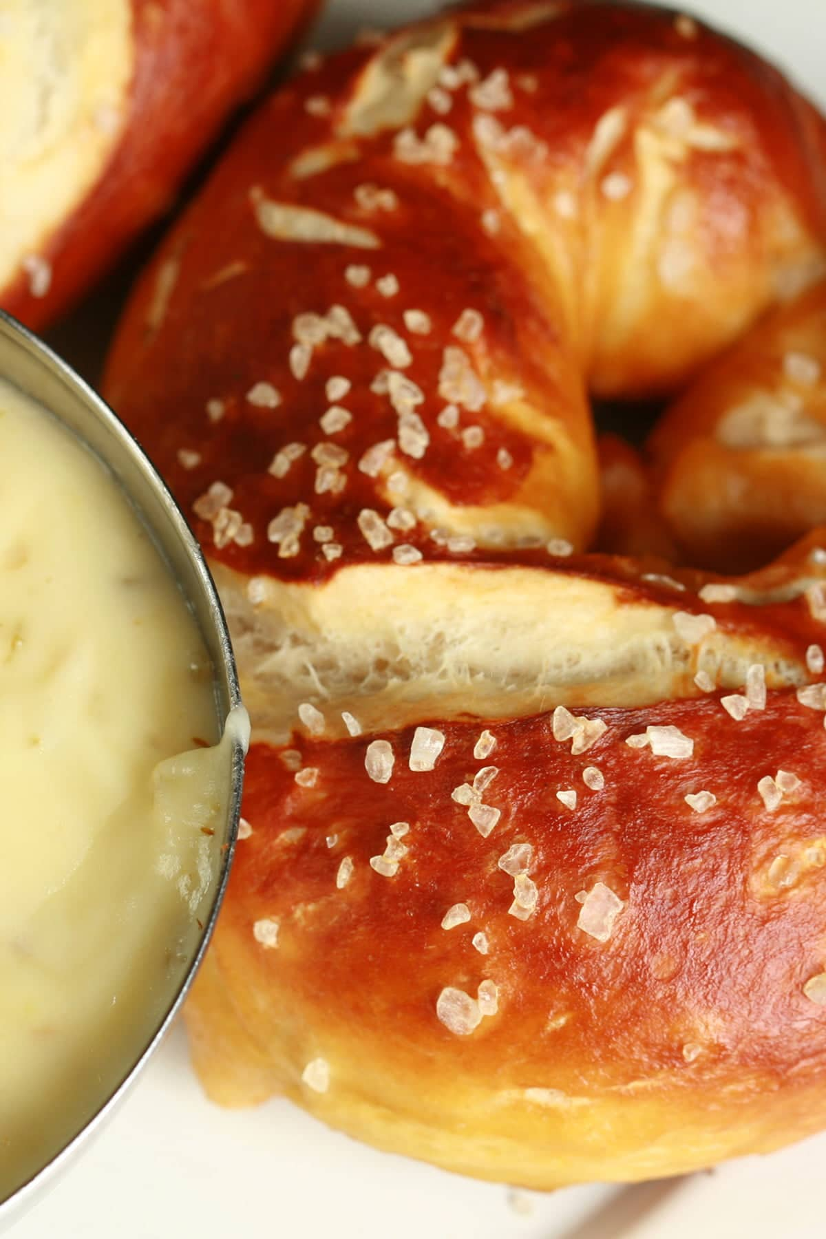 A very close up photo of a pretzel next to a bowl of jalapeno cheese dip.