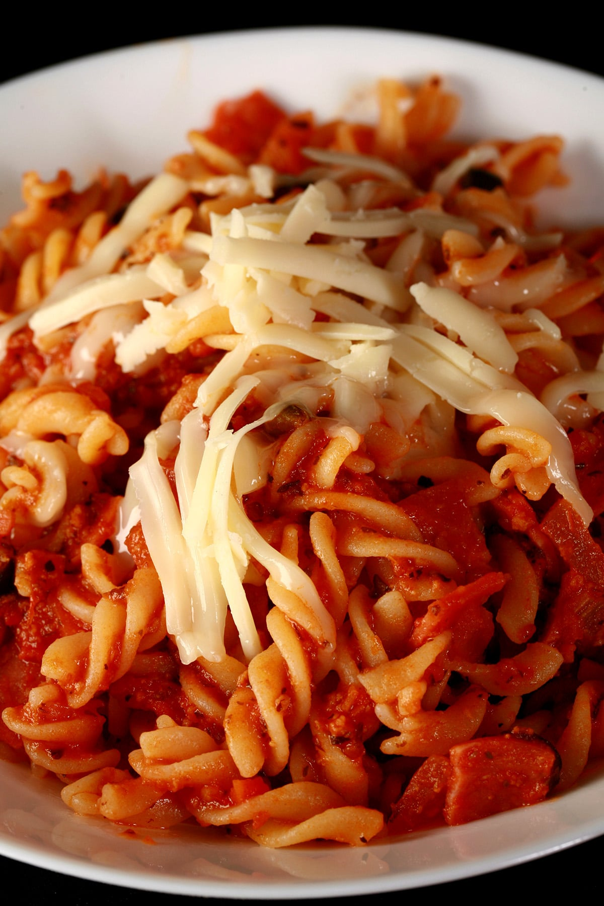 A bowl of pasta in red sauce, with bits of pepperoni and sliced black olives visible.