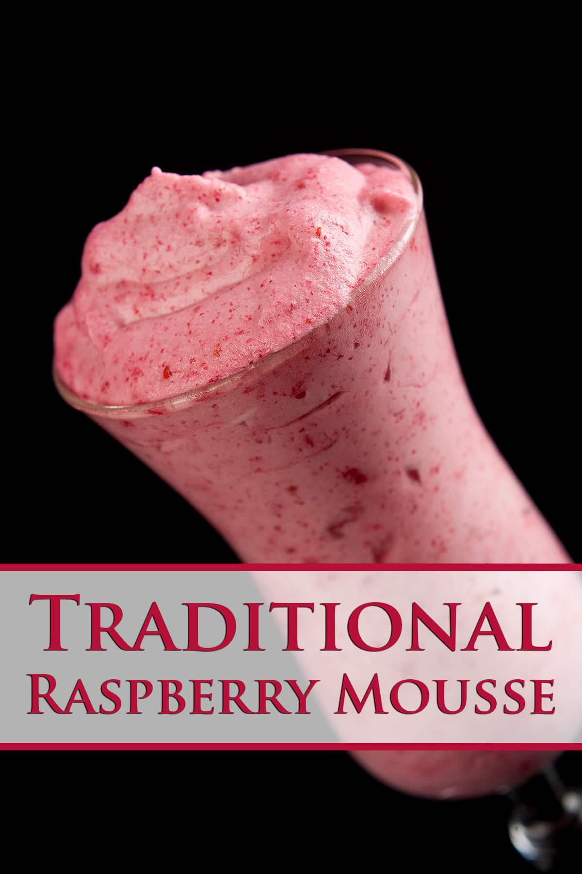 A tall, tulip shaped cocktail glass isfilled with a deep pink raspberry mousse, against a black background, The text overlay says Traditional Raspberry Mousse.