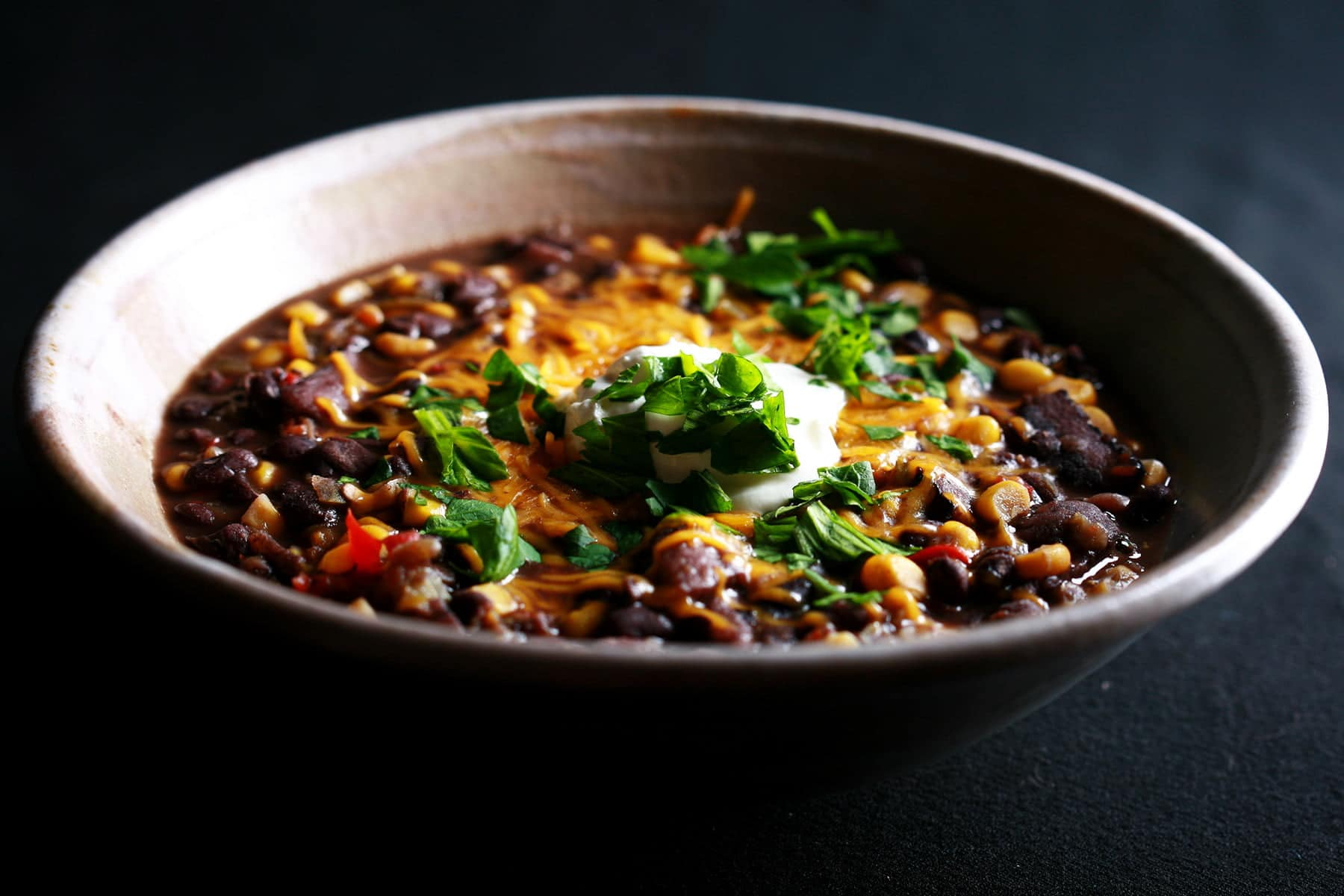 A large bowl of a colourful corn and black bean soup. Corn and red peppers are visible throughout the soup, and there is grated cheddar cheese, soup cream, cilantro, and green onion slices on top.