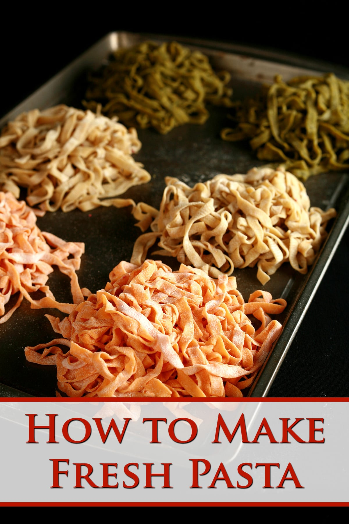 A parchment lined baking sheet with mounds of red, white, and green coloured fresh linguini on it.