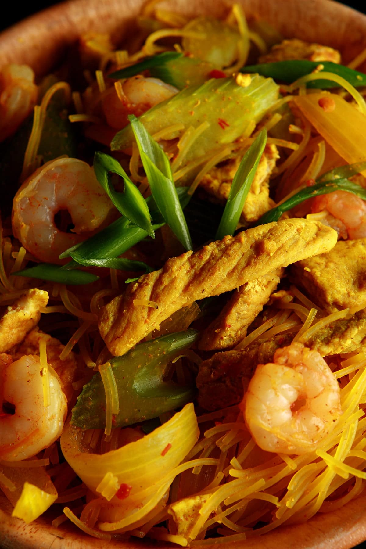 A large bowl of Singapore Mai Fun - curried vermacelli noodles with onion, celery, chicken, and shrimp visible throughout.