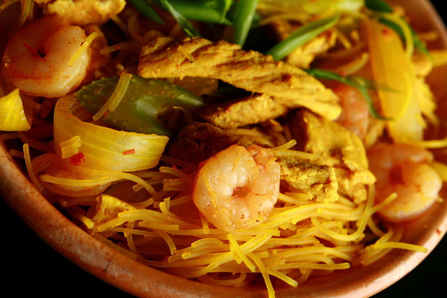 A large bowl of Singapore Mai Fan - curried vermacelli noodles with onion, celery, chicken, and shrimp visible throughout.