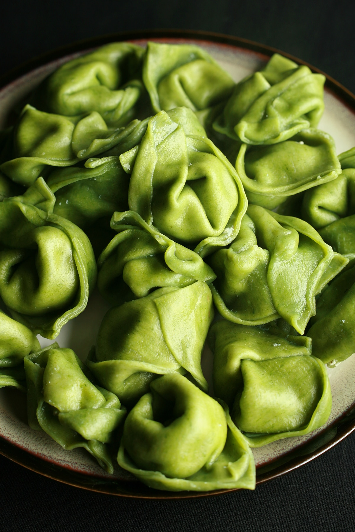 A plate of bright green spinach tortellini.