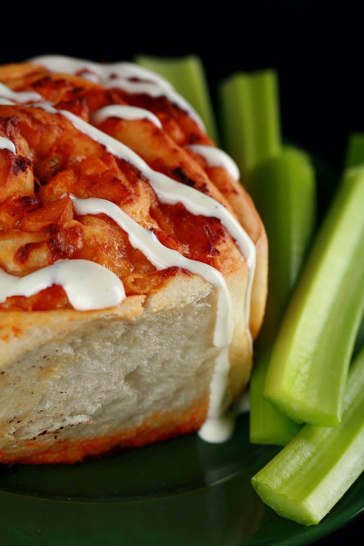 A close up photo of a buffalo chicken bun - like a cinnamon bun, but with a buffalo chicken filling instead. It is drizzled with ranch dressing, and has celery sticks on the side.
