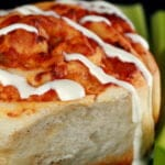 A close up photo of a buffalo chicken roll - like a cinnamon bun, but with a buffalo chicken filling instead. It is drizzled with ranch dressing, and has celery sticks on the side.