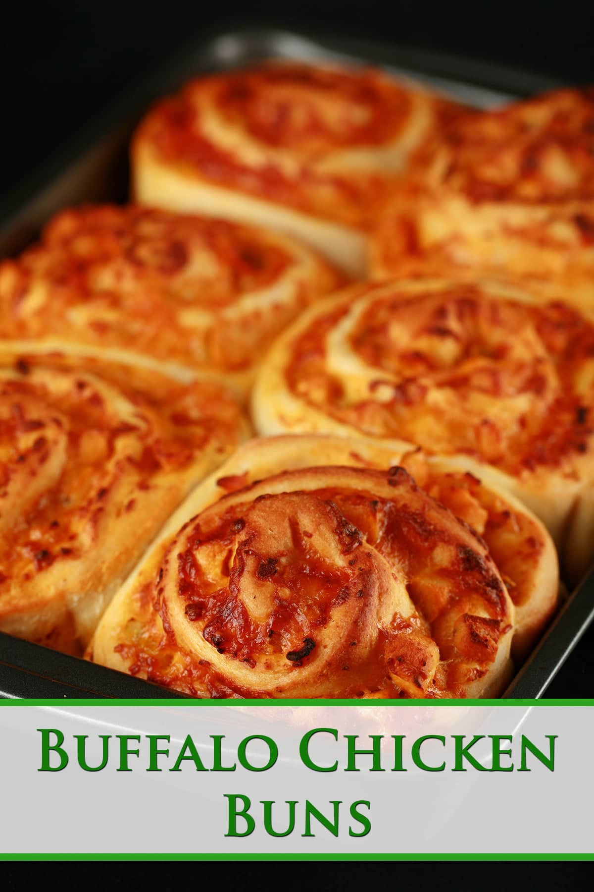 A pan of 6 baked buffalo chicken buns. They resemble cinnamon buns, but with a buffalo chicken and cheese filling.