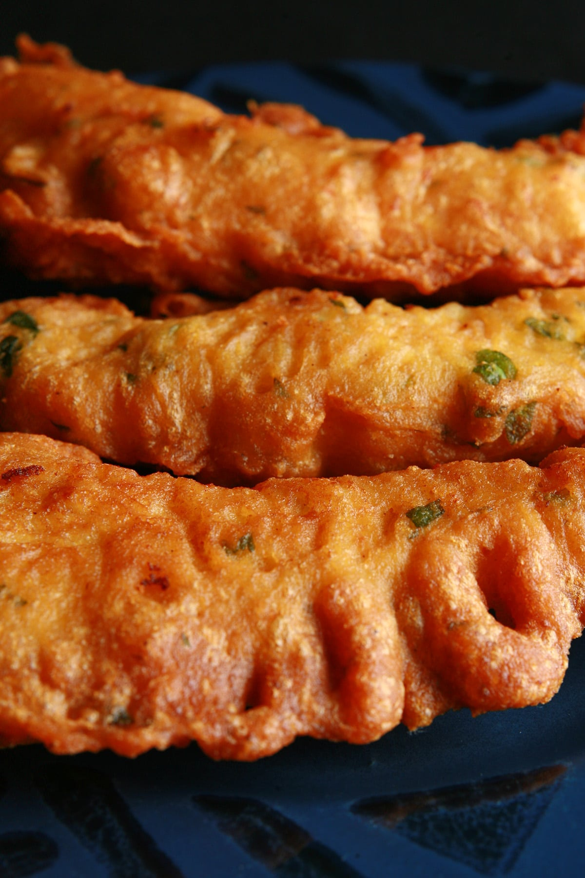 3 long fingers of chicken pakora on a blue plate. Bits of cilantro are visible in the fried batter.