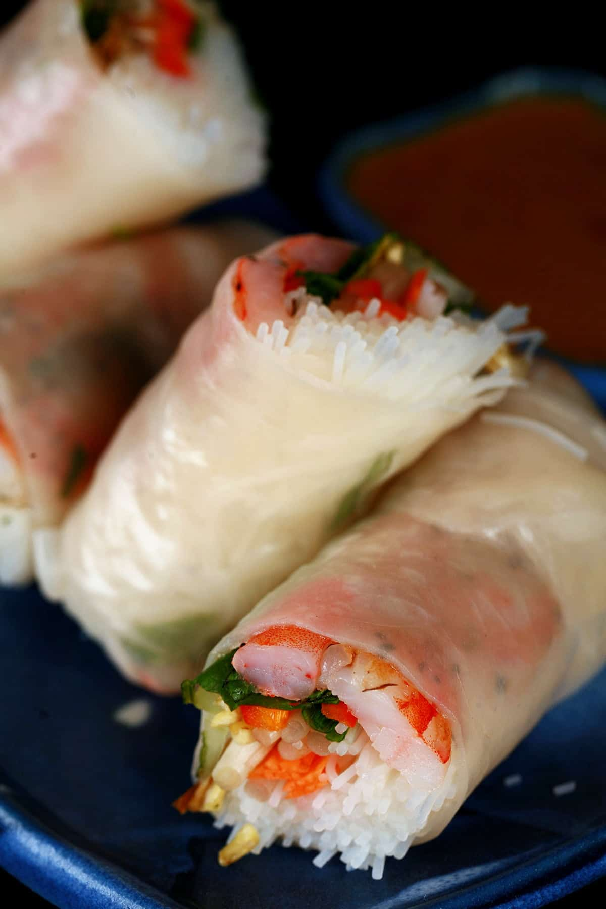 4 pieces of shrimp spring rolls are arranged on a blue plate.