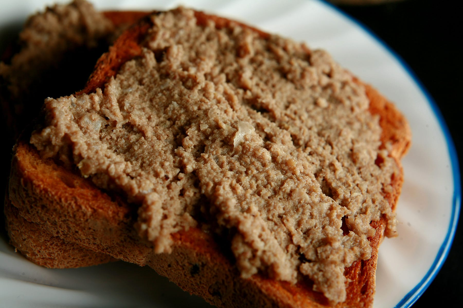 A slice of toast spread with cretons, on a small white plate.