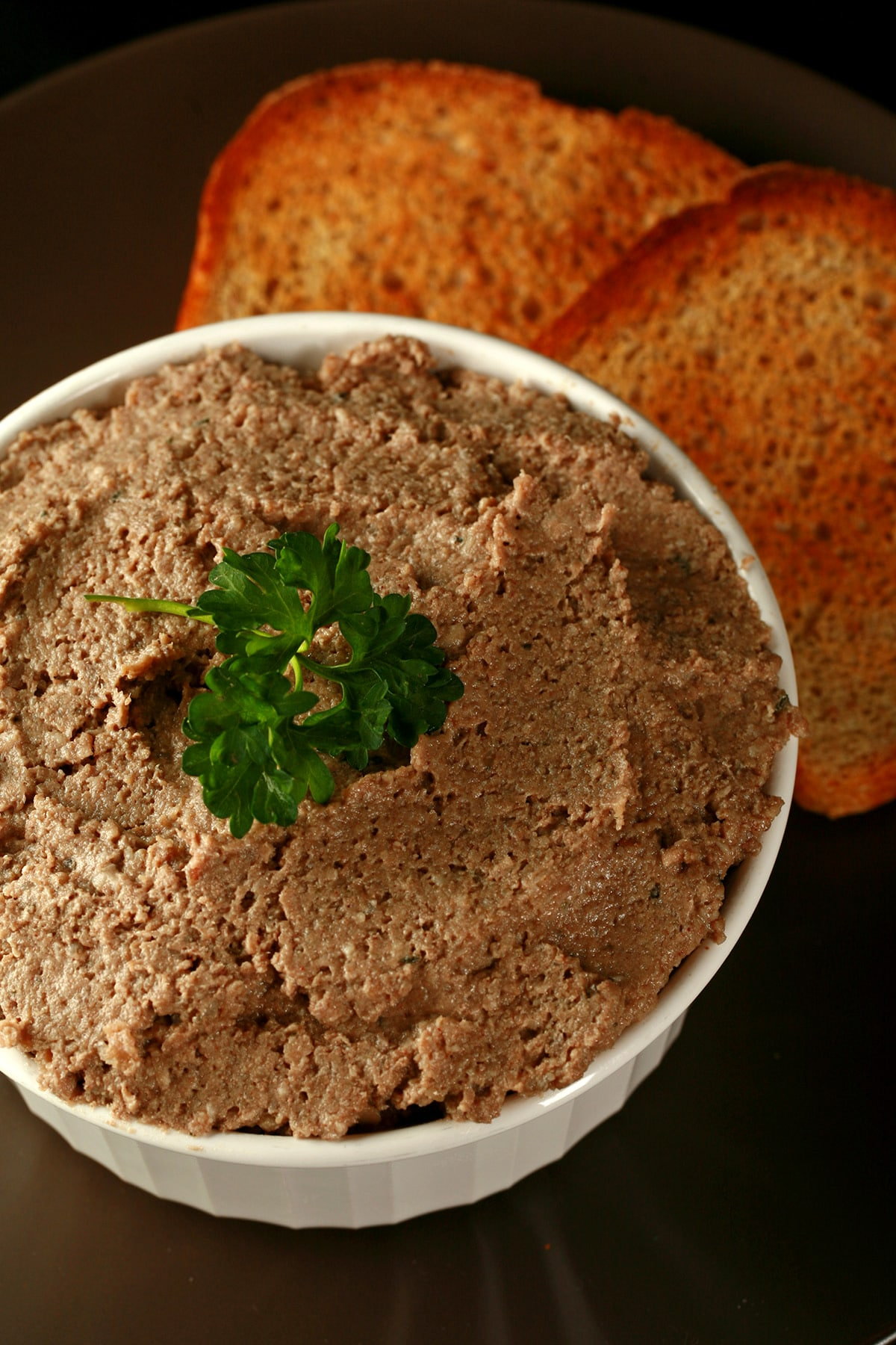 A pot of cretons - a French Canadian pork pate - in a small white ramekin, next to slices of toast.