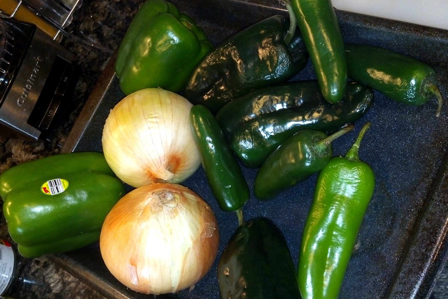 Onions and a variety of peppers, on a roasting pan.