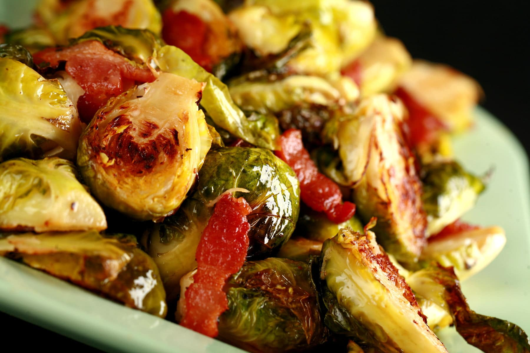 A pale green platter, mounded with roasted Brussels Sprouts. Chopped Bacon is visible throughout.