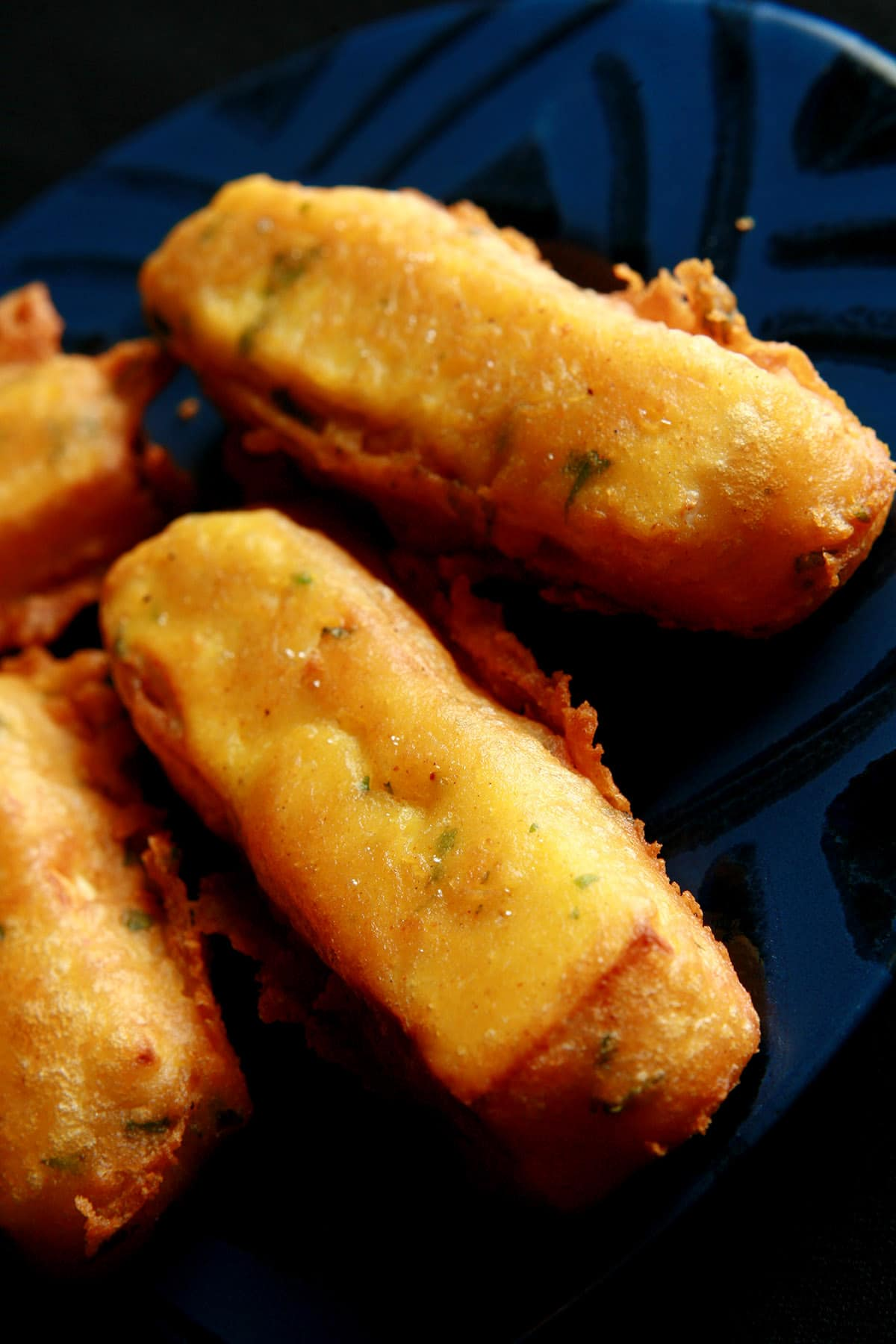 A close up view of several sticks of paneer pakora - Indian fried cheese sticks. Bits of cilantro are visible in the golden yellow batter.