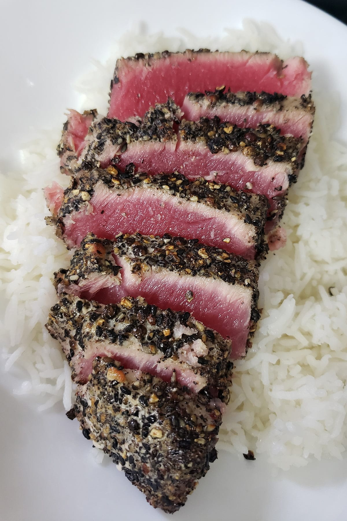 A pepper crusted tuna steak, cooked rare, has been sliced and fanned out over some rice.