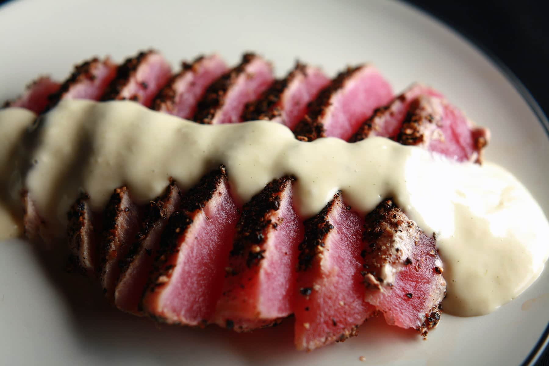 Pepper crusted tuna with wasabi cream sauce. The tuna steak has been cooked rare, sliced up, and fanned out on the plate before being topped with the sauce.