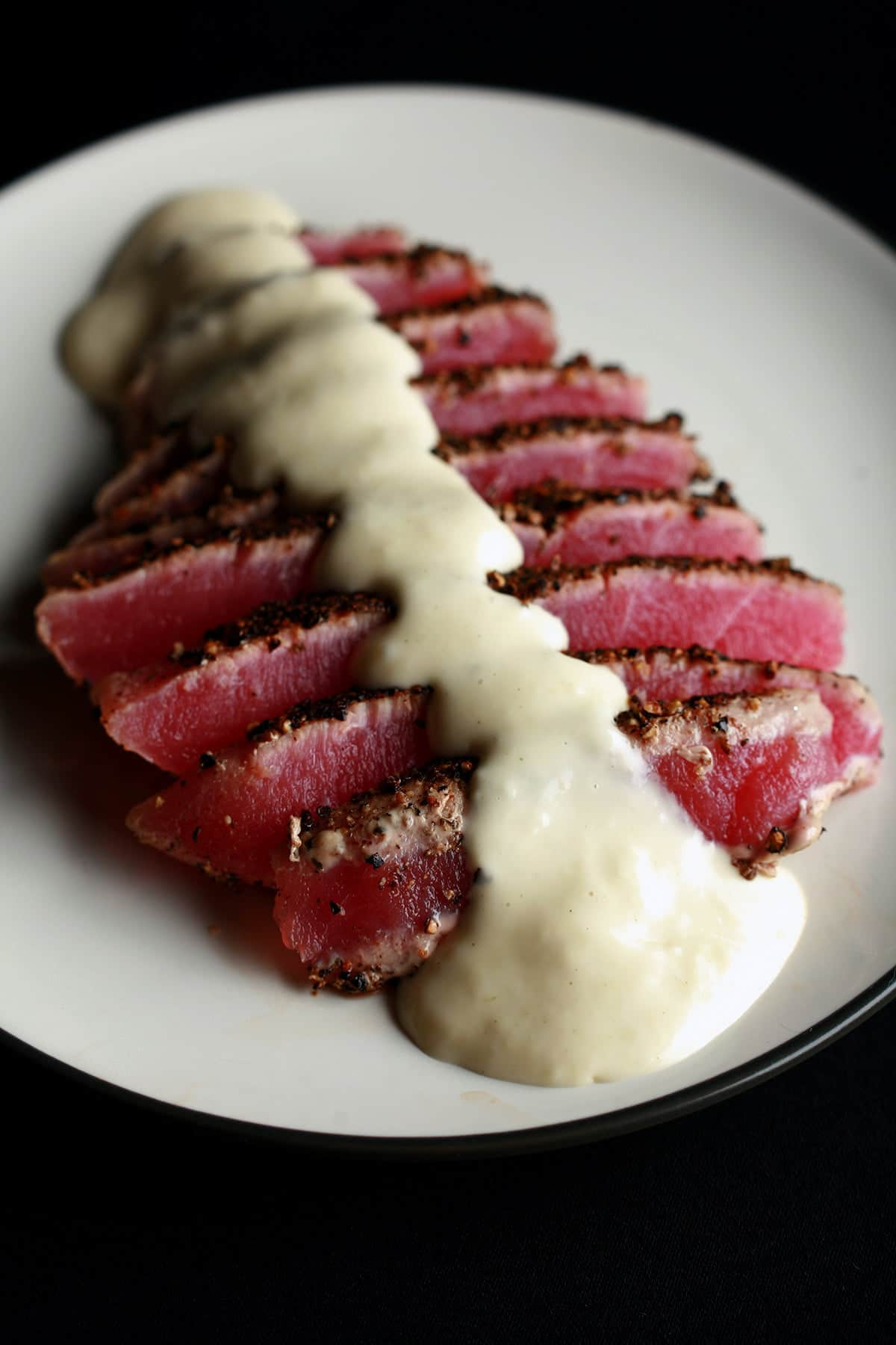 A pepper crusted tuna steak - rare - that has been sliced up, fanned out on a small white plate, and drizzled with wasabi cream sauce.