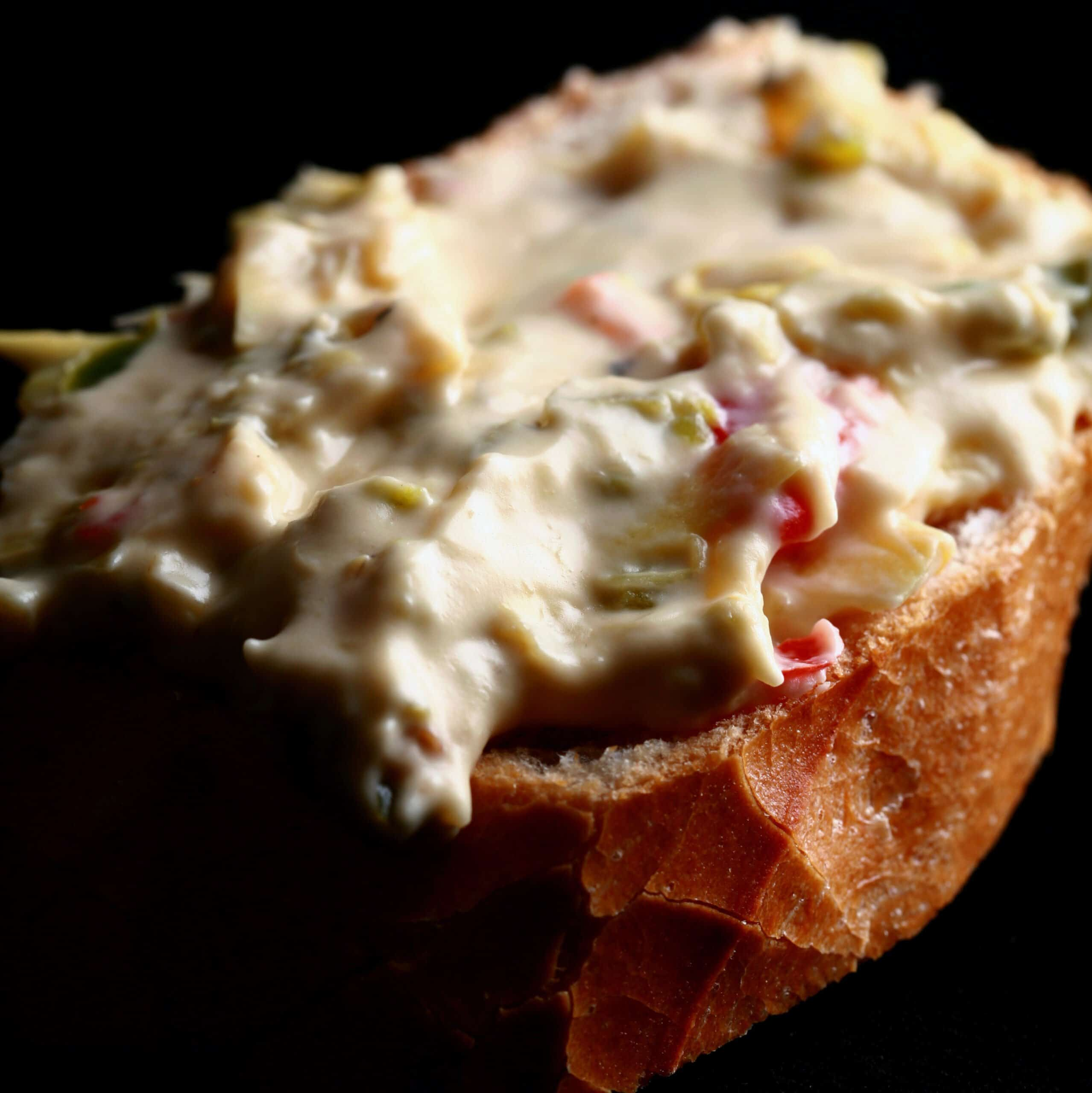 A slice of baguette spread with Backfire dip - a chunky jalapeno artichoke cheese dip.