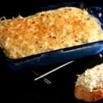 A small, blue, rectangular glass pan, filled with a golden brown cheese dip. In the foreground is a slice of baguette spread with the artichoke jalapeno cheese dip.