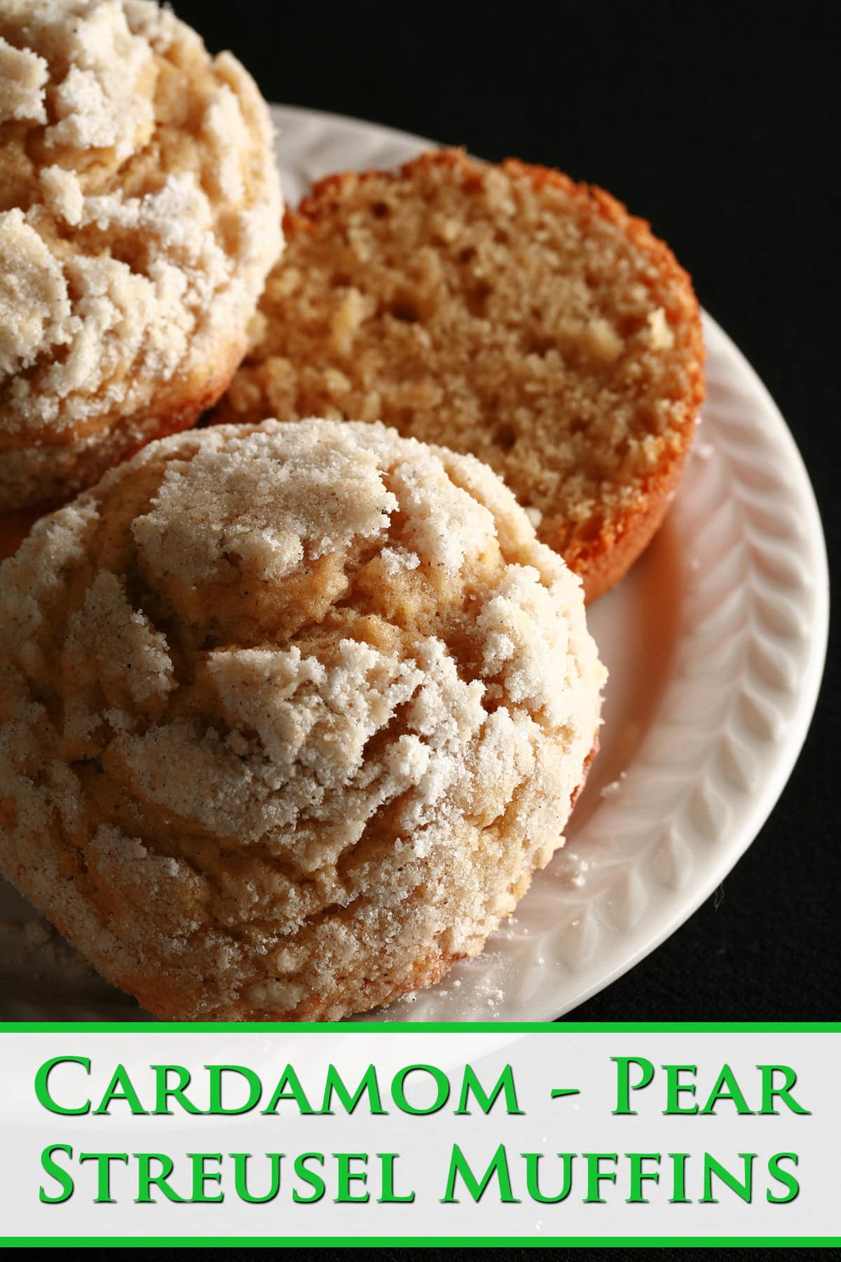 Two cardamom pear streusel muffins on a small white plate.
