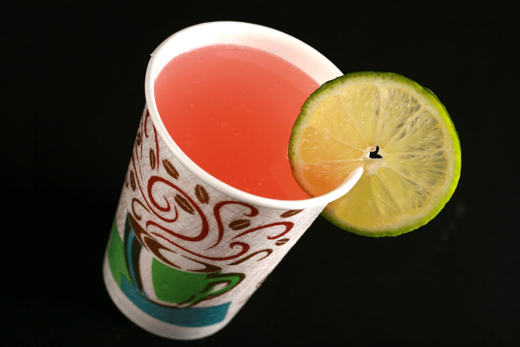 The Drinking In LA - a light pink fizzy cocktail in a hotel room disposable coffee cup.  It is garnished with a slice of lime.