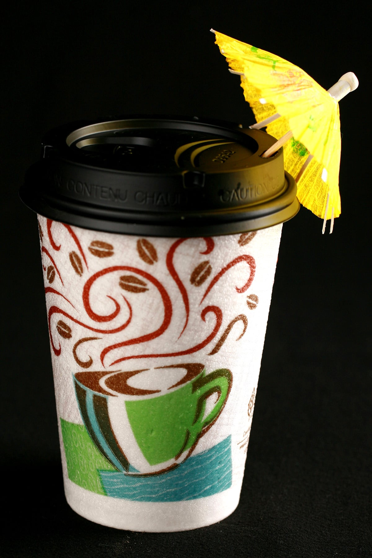 The Drinking In LA - a light pink fizzy cocktail in a hotel room disposable coffee cup. It is garnished with a yellow paper umbrella.