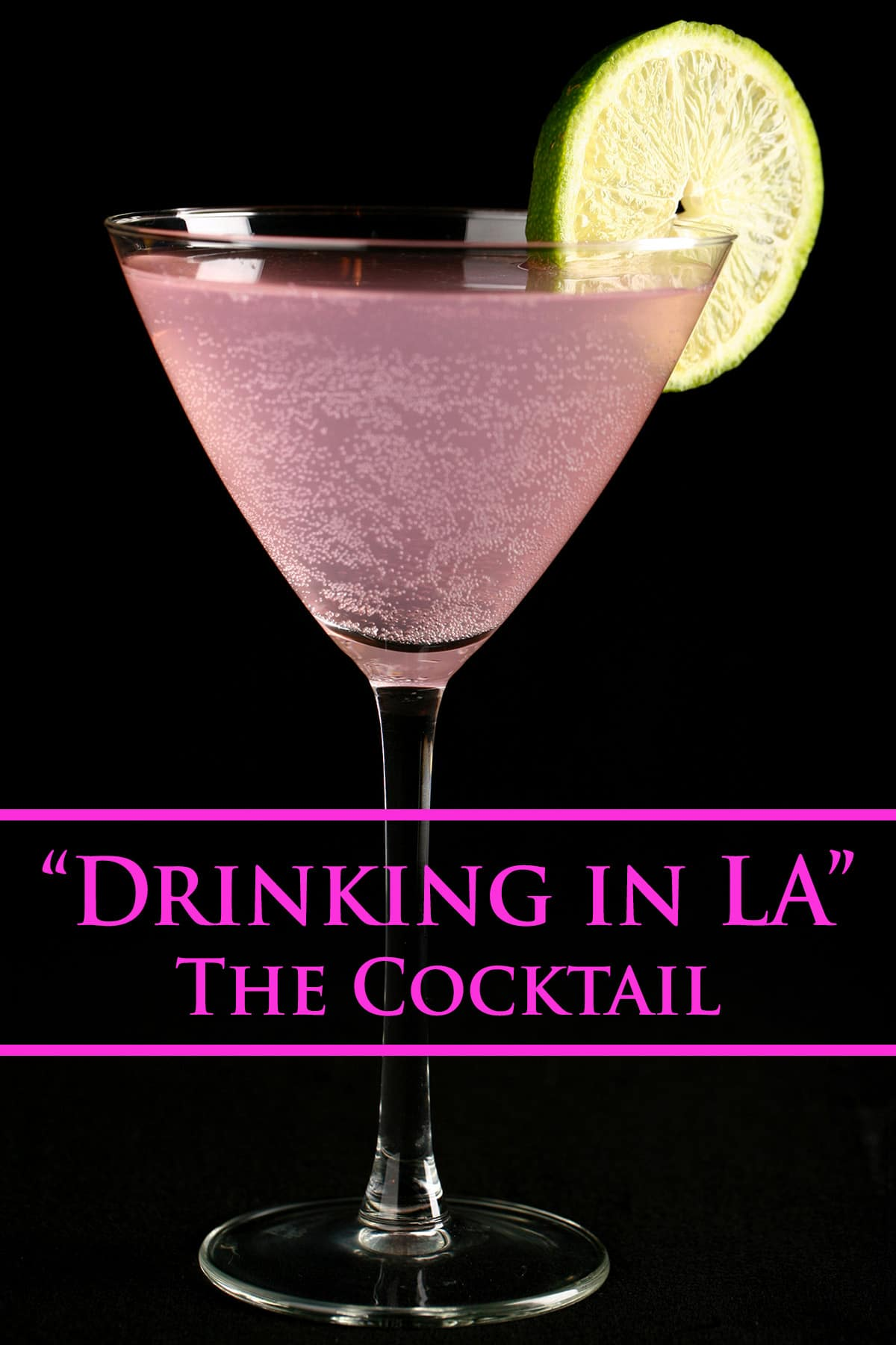 The Drinking In LA - a light pink fizzy cocktail in a martini cocktail glass. It is garnished with a slice of lime.
