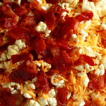 A close up view of Porter's Epic Popcorn - Popcorn with bacon, cheese, and jalapeno powder on it.