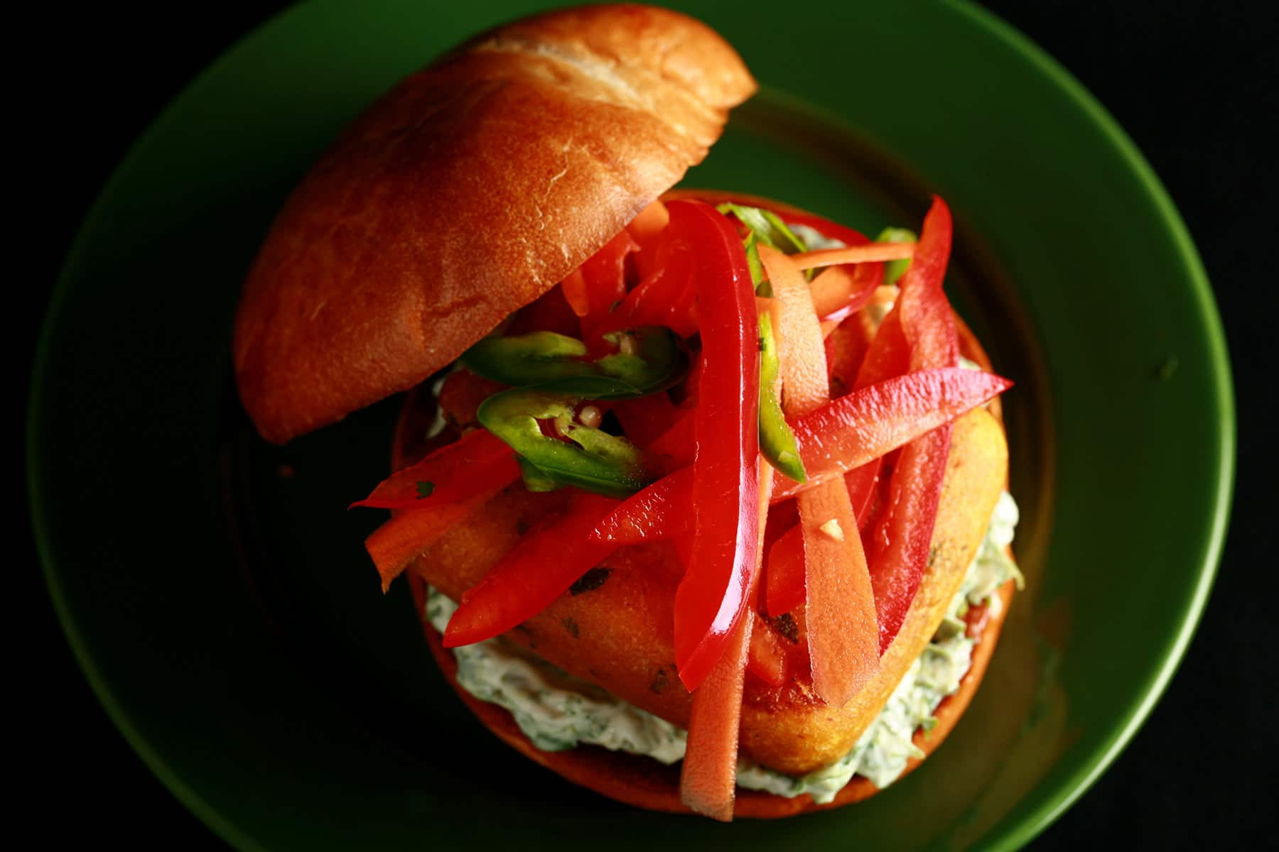 A very close up view of a paneer burger - a pakora battered patty of paneer, with cilantro-mint mayonnaise and a pickled slaw made of red peppers, carrots, and jalapenos, on a bun.