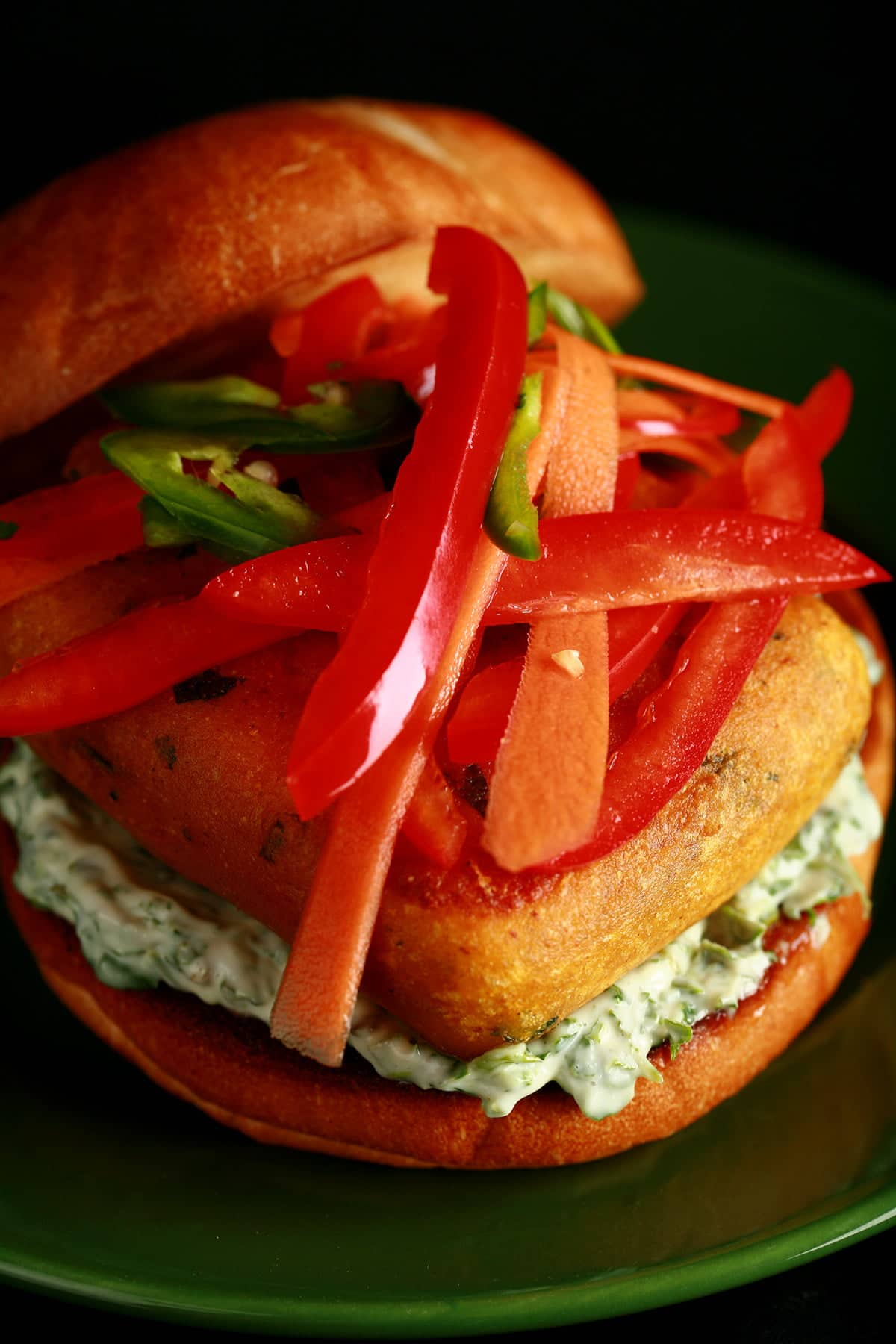 "A very close up view of an ""Indian Cheeseburger"" - a pakora battered patty of paneer, with cilantro-mint mayonnaise and a pickled slaw made of red peppers, carrots, and jalapenos, on a bun."