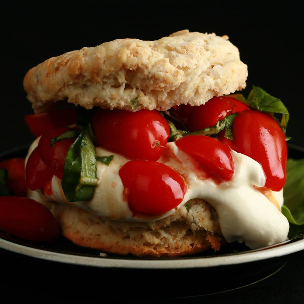 """A baking powder biscuit """"sandwich"""" on a small black plate.  The biscuit has soft white cheese, cherry tomatoes, and fresh basil as its filling."""