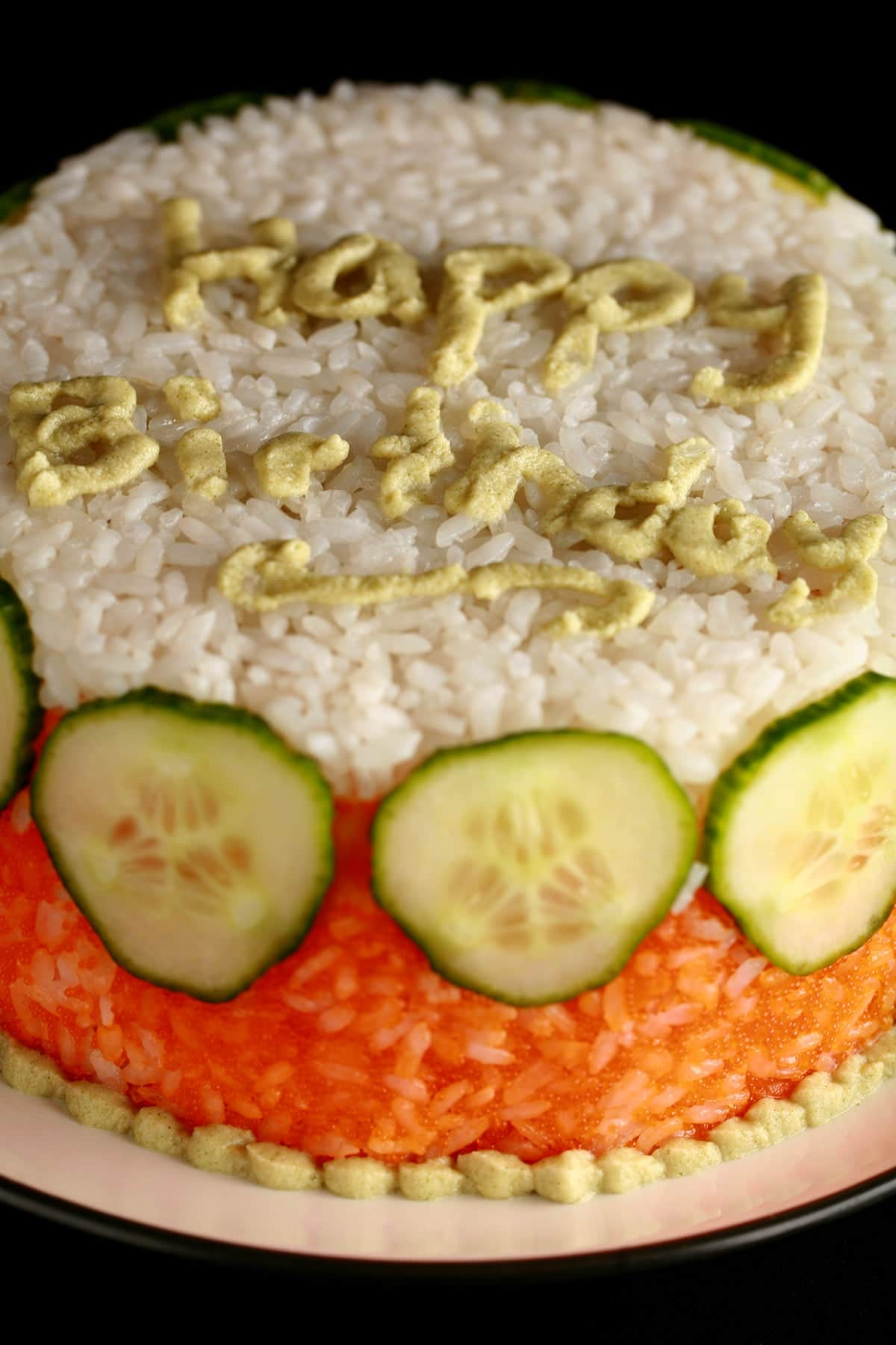 """A small """"birthday cake"""" made of white and orange rice and cucumber slices. """"Happy Birthday"""" is written on the top, in wasabi."""