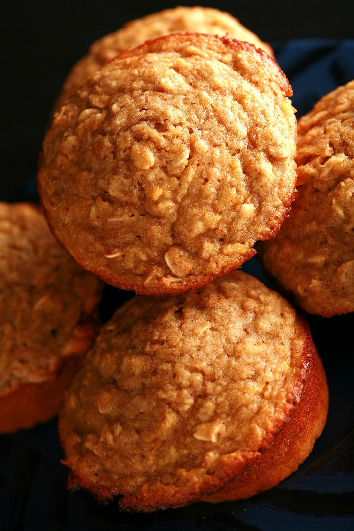 A small blue plate with a black geometric design around the edge is stacked with these healthier apple oatmeal muffins.