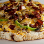 A close up shot of a large biscuit crust topped with bacon, green onions, mushroooms, and cheese.