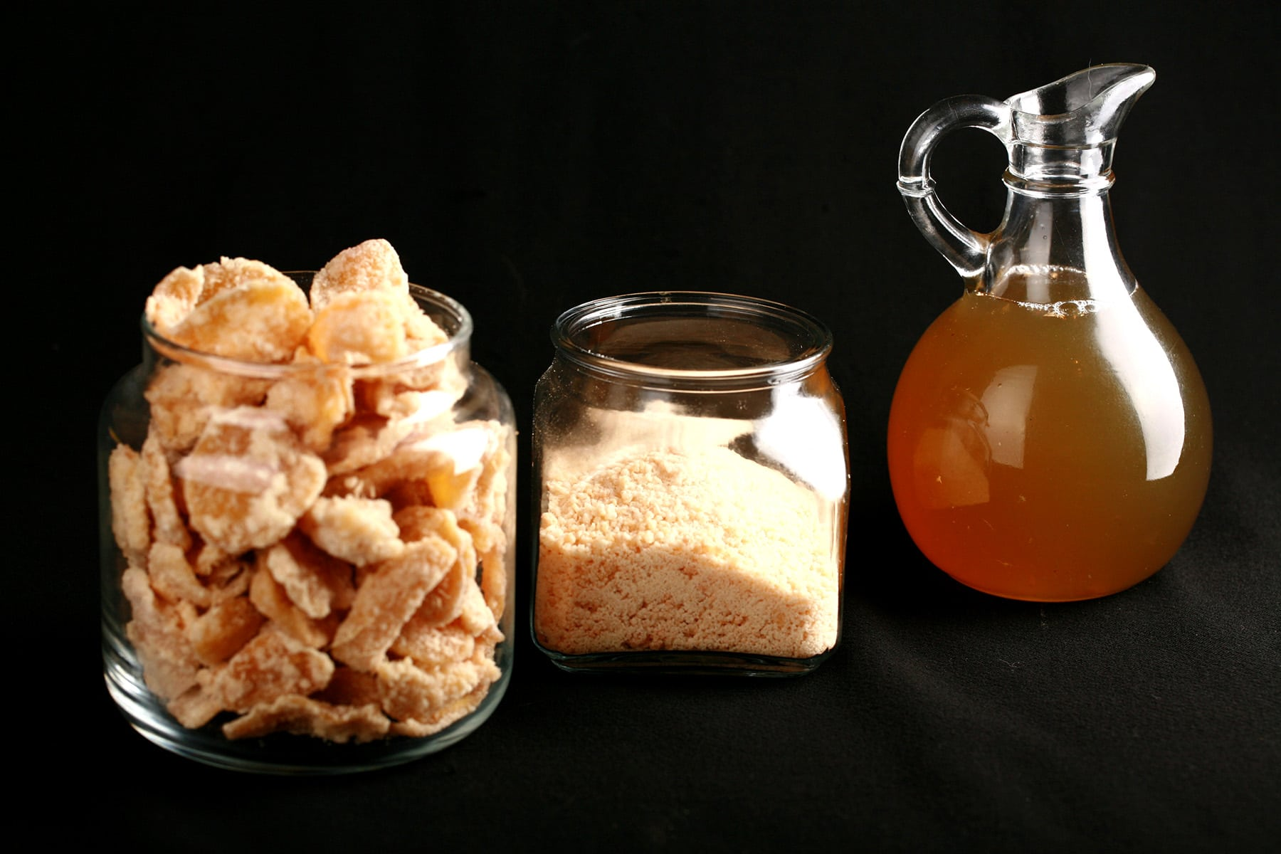 A glass jar of ginger sugar, a taller glass jar filled with candied ginger, and a small bottle of ginger syrup.