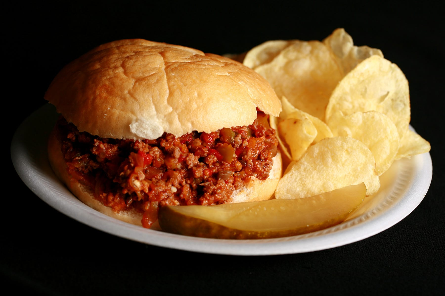 A Sloppy Joes sandwich on a paper plate, with chips and a pickle spear.