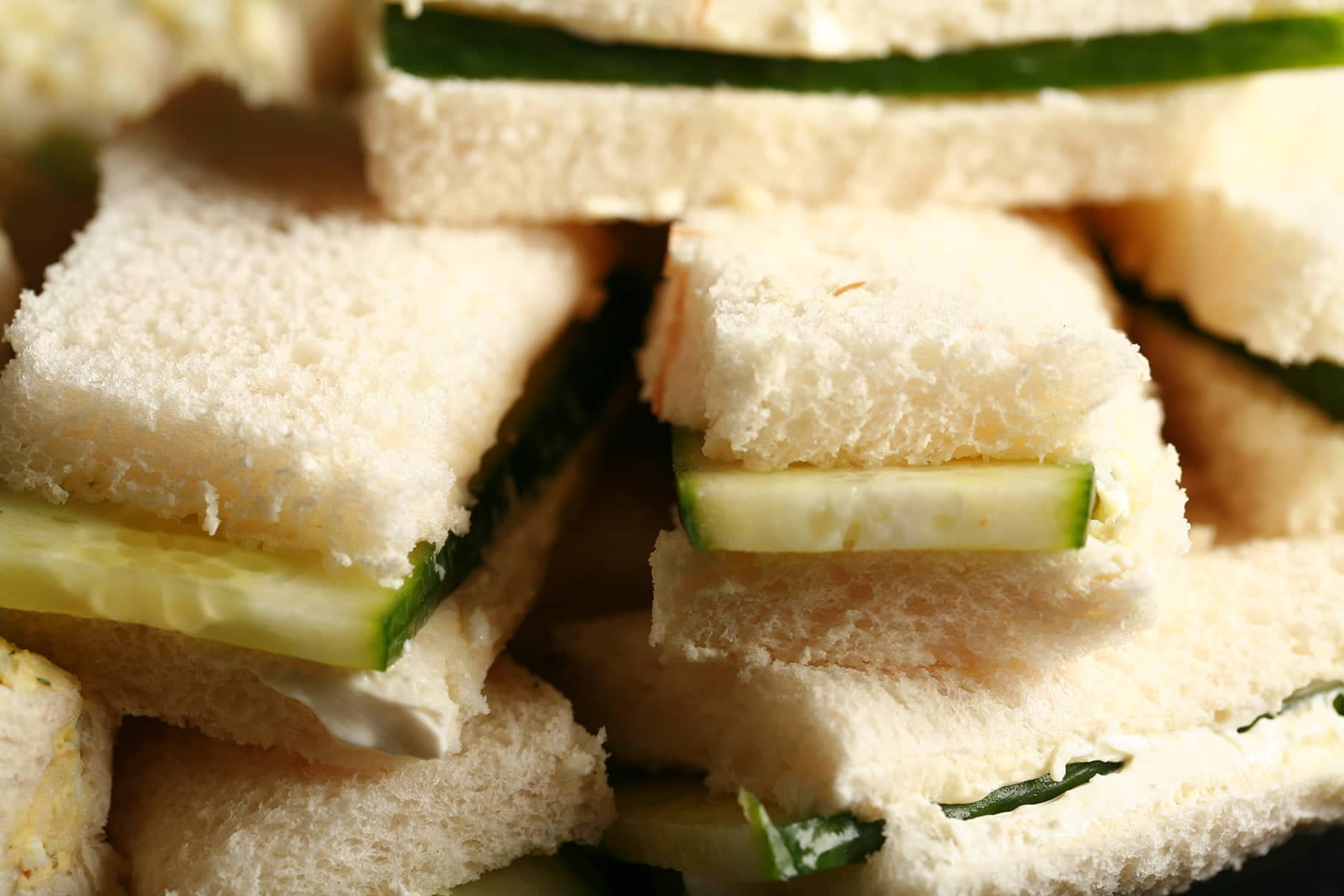 A close up view of cucumber cream cheese finger sandwiches.
