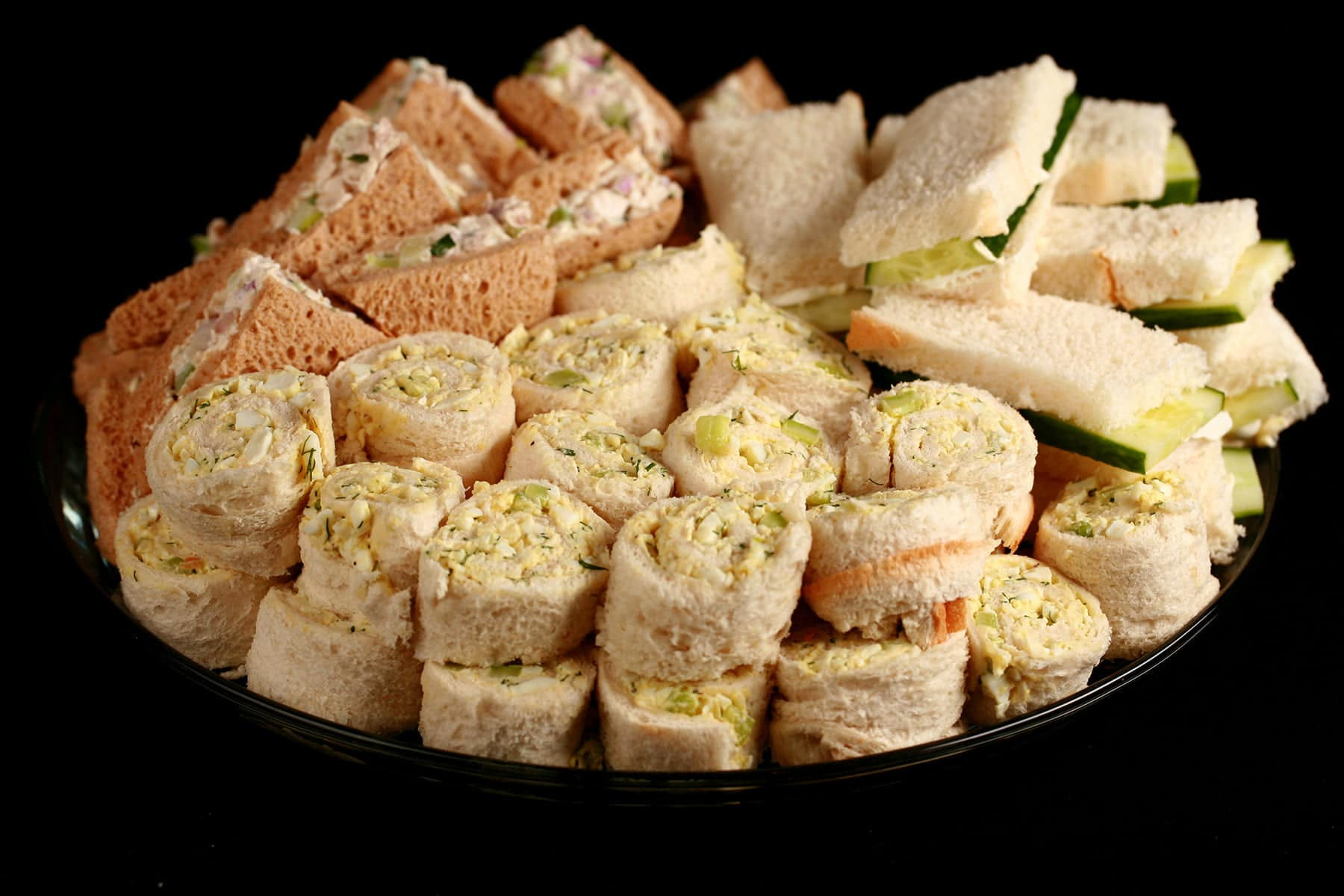 A large platter of fancy tea sandwiches. Cucumber cream cheese finger sandwiches, egg salad pinwheels, and tarragon chicken salad triangles.