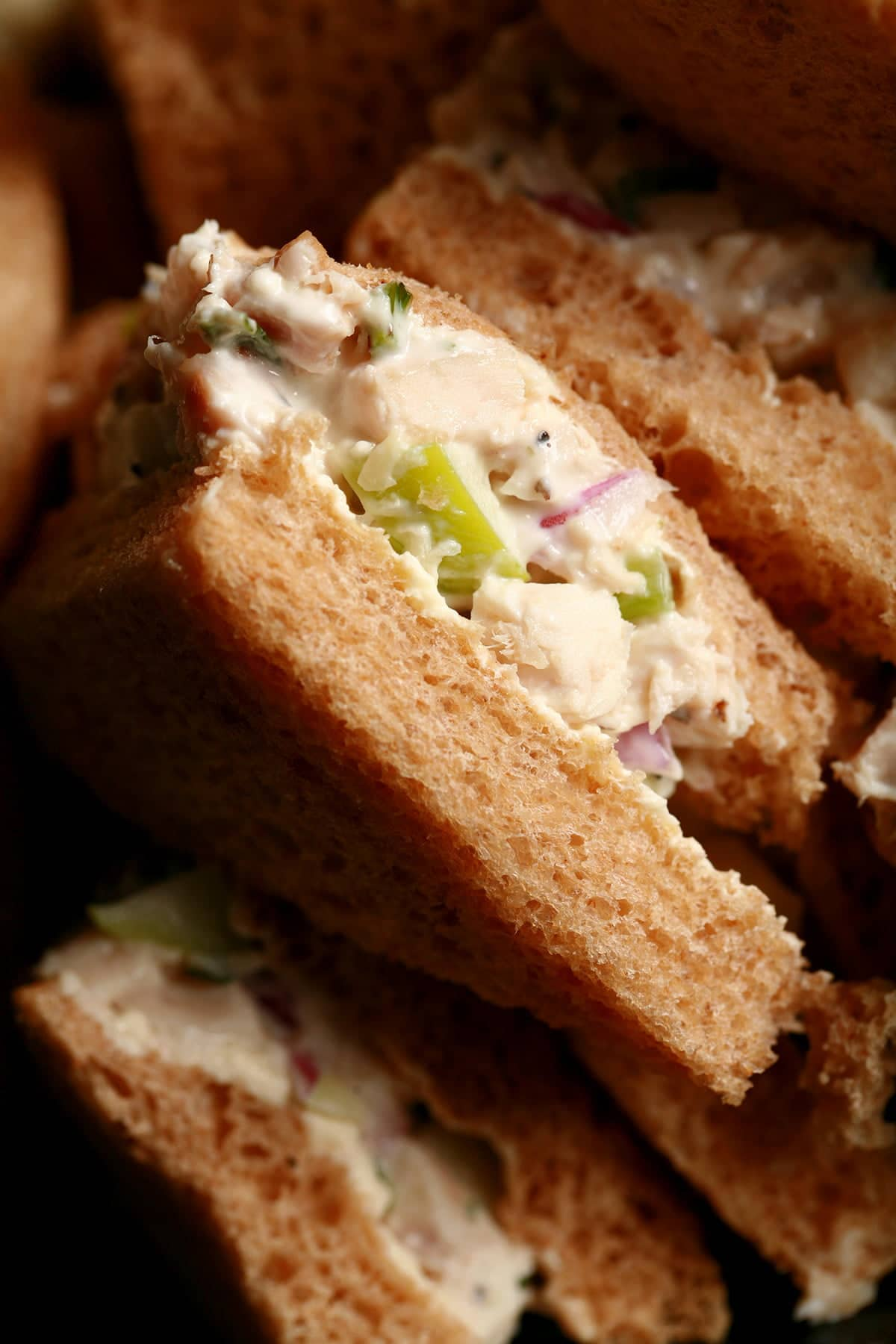 A close up view of triangle tea sandwiches filled with tarragon chicken salad.