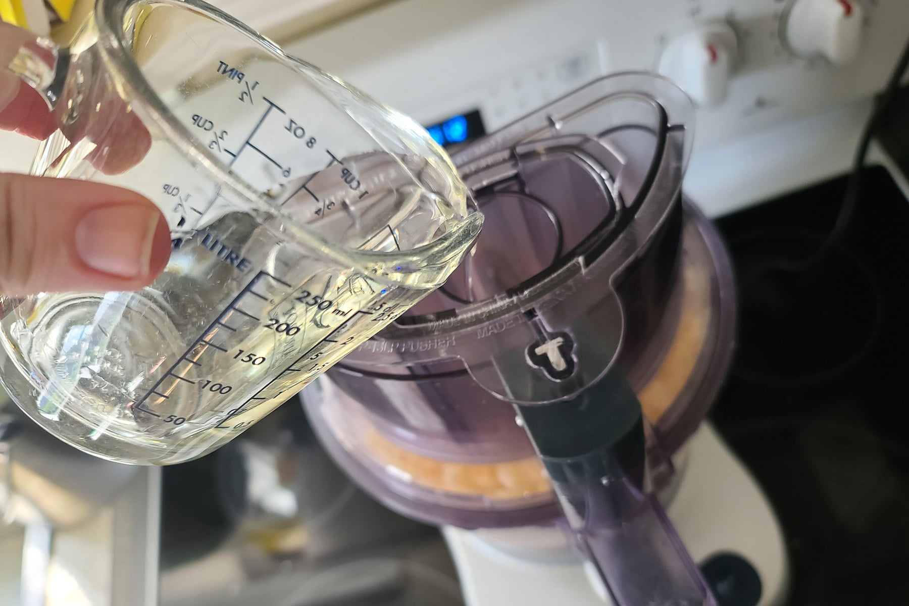 White wine being poured into the food processor.